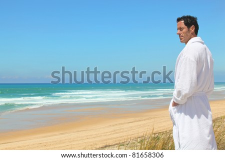Man on the beach in towel robe - stock photo