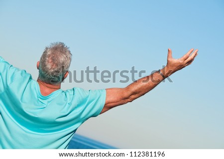 Man on the beach praising - stock photo