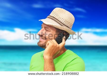 man on the beach talking on the phone - stock photo
