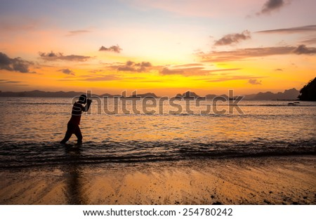 man on the beach with a camera on a background of a sunset