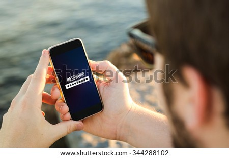 man on the coast entering password on his smartphone . All screen graphics are made up. - stock photo