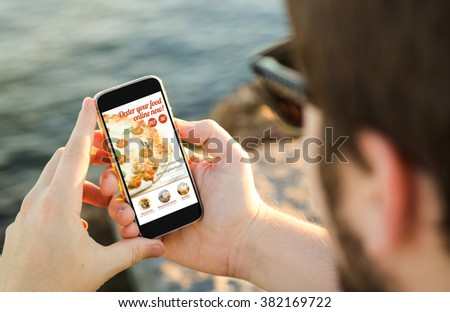 man on the coast using his smartphone to order pizza online. All screen graphics are made up. - stock photo