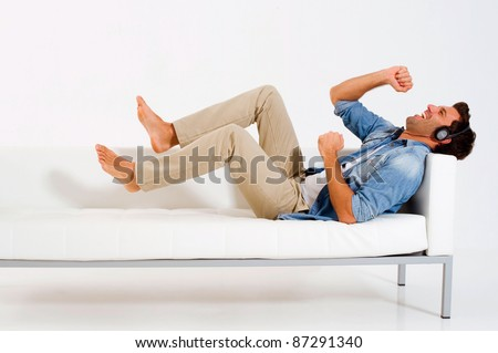 man on the couch listening music with headphones - stock photo