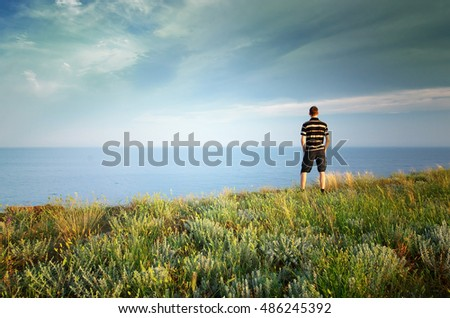 Man on the edge. Cliff of mountain and sea. Conceptual scene.