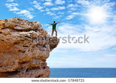 Man on the edge of cliff. Emotional scene. - stock photo