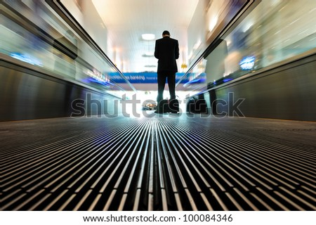 Man on the escalator in airport - stock photo