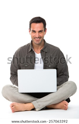 Man on the floor, smiling at camera and working with his laptop - stock photo
