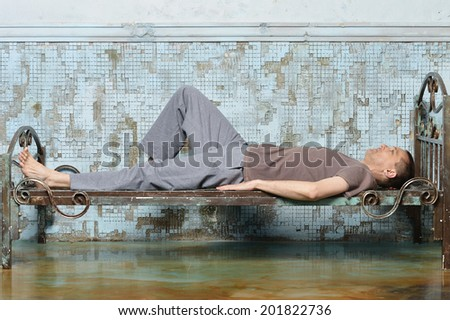 Man on the metal bed in prison - stock photo