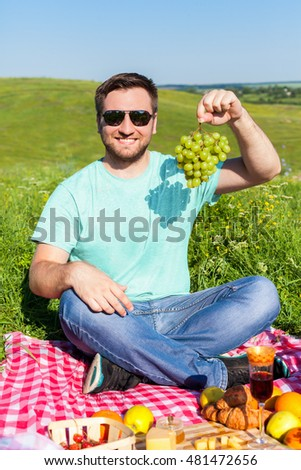 Man on the picnic alone is going to eat grape