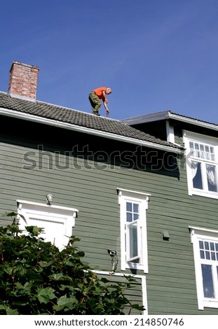 Man on the roof of his house inspecting his chimney - stock photo