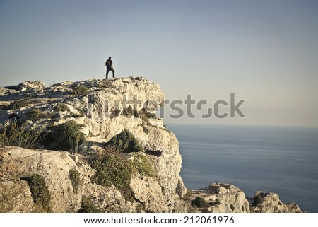 man on the top of a rock admiring the seaside - stock photo