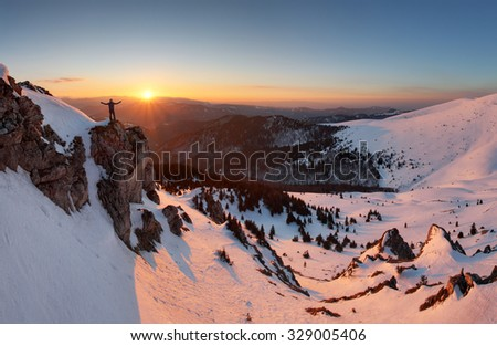Man on top as silhouette in mountain - stock photo
