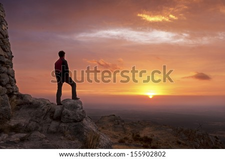 Man on top of a mountain standing contemplates the dawn - stock photo