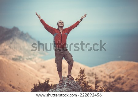 Man on top of mountain holding arms up