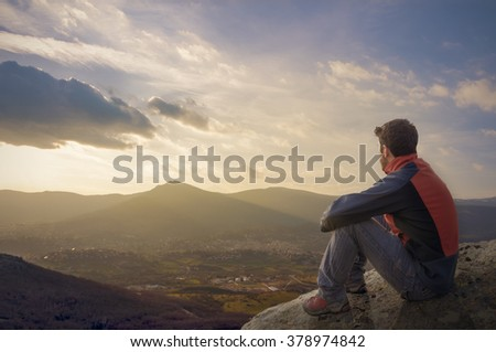 Man on top of mountain sitting on the rock watching a nice sunrise in the village - stock photo