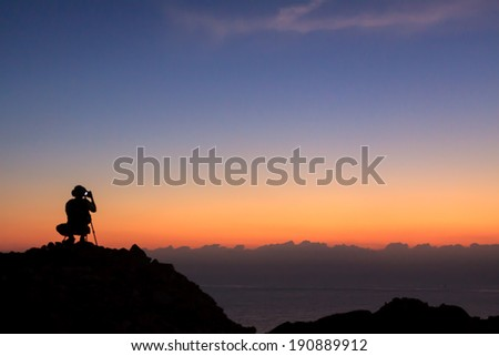 Man on top of the mountain taking photographic at sun rise  - stock photo