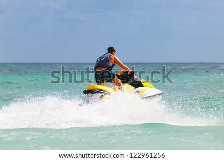 Man on Wave Runner turns fast on the water - stock photo