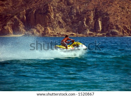 Man on wave running motor boat.  He moving very quickly.  There is a large spray of water behind the boat.  The water is deep blue.