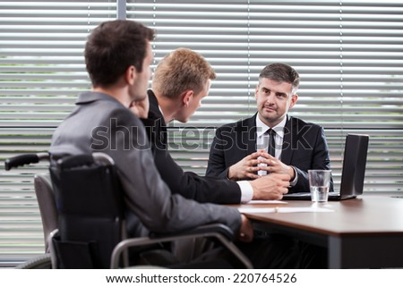 Man on wheelchair at the table talking business - stock photo