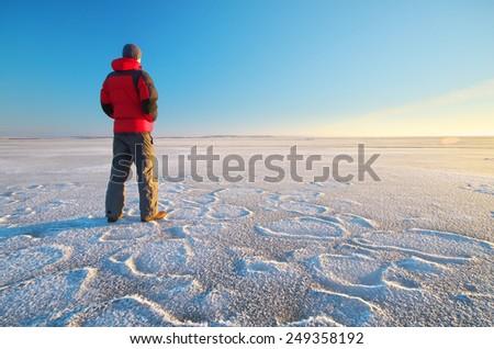 Man on winter ice. Hiking scene. - stock photo