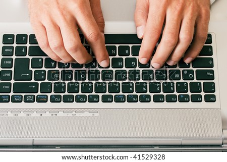 Man (only hand to be seen) using a computer keyboard typing