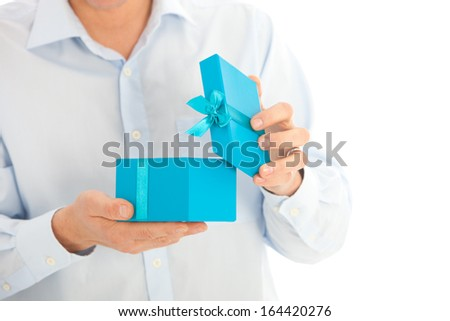 Man opening a birthday or Christmas gift in a colourful turquoise blue box decorated with a ribbon and bow, close up torso view of his hands and the box - stock photo