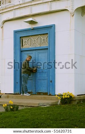 Man opening blue metal door - stock photo
