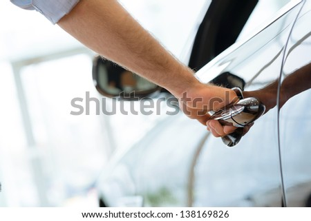 man opens the door to a new car, car inspection in the showroom - stock photo