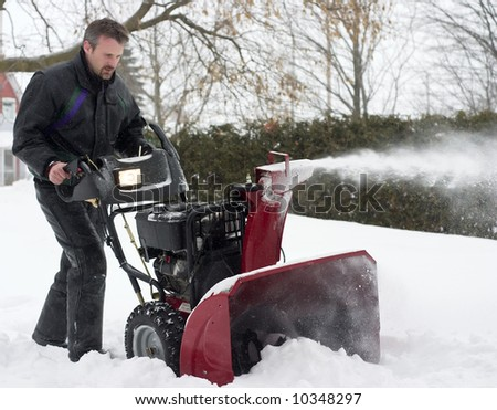 man operating snow blower in winter - stock photo