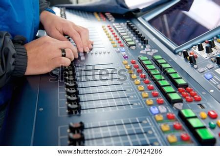 Man operating sound levels on audio mixer - stock photo