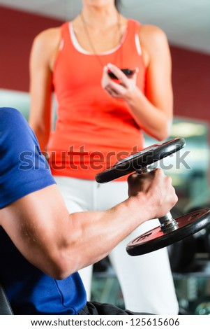 Man or Bodybuilder with his personal fitness trainer in the gym exercising with dumbbells, closeup - stock photo