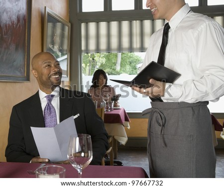 Man ordering in restaurant - stock photo