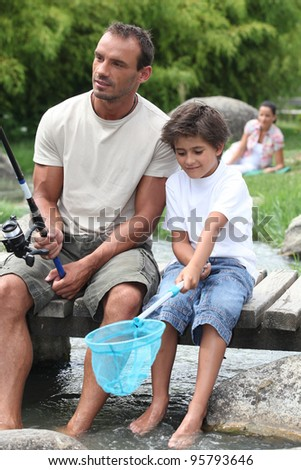 Man out fishing with his son - stock photo