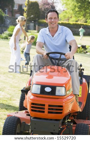 Man outdoors driving lawnmower smiling with family in background - stock photo