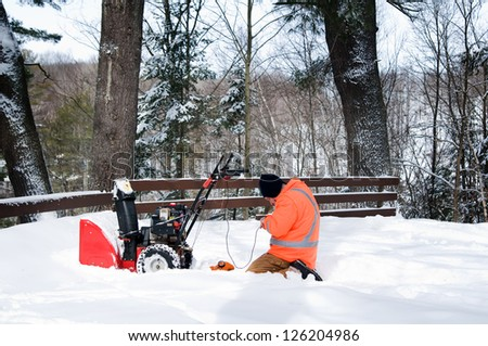 man outdoors in the snow fixing a snow-blower - stock photo