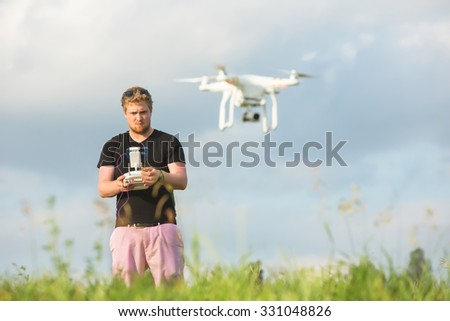 Man outdoors with remote control and flying surveillance drone - stock photo