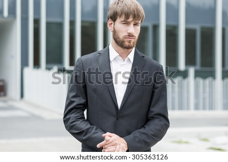 Man outside company is standing with solemn expression - stock photo