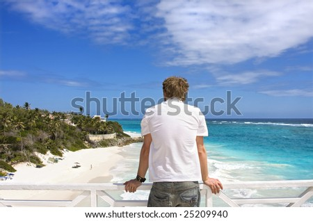 Man overlooking beach from balcony