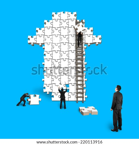 man oversee teamwork for puzzles in arrow shape isolated on blue - stock photo