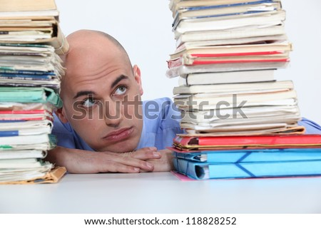 man overwhelmed with folders
