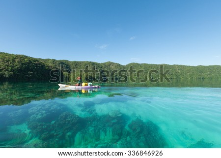 Man paddling his kayak on clear turquoise water of a tropical lagoon, Palau, Micronesia