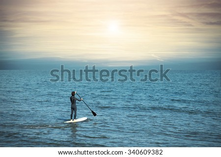 man paddling on a board at the sea at sunset - stock photo