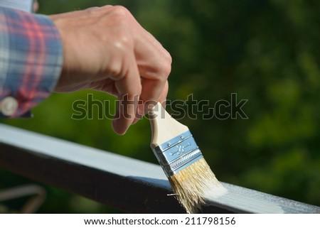Man painting a guard rail on a balcony - stock photo