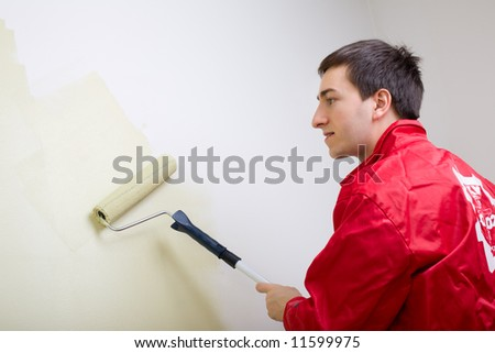 Man painting a wall. Painter in red overall painting wall in light green color