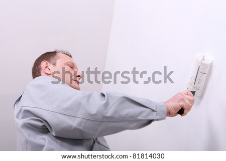 Man painting an interior wall white - stock photo