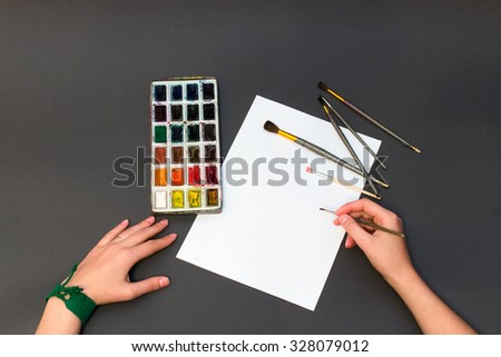 man painting brush on a white sheet of paper, next to which is a set of colors for painting
