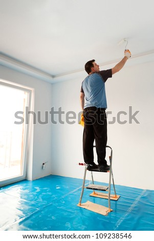 Man painting ceiling of new apartment