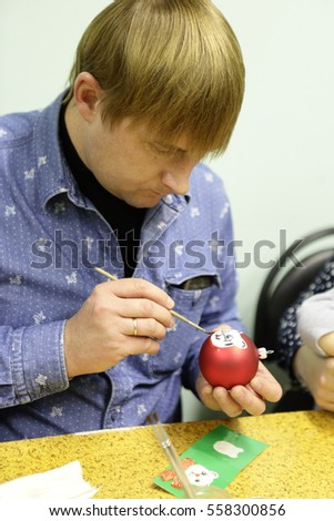 Man painting Christmas toy at table in class