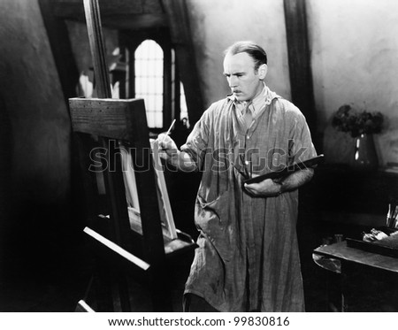 Man painting on an easel with a paintbrush - stock photo