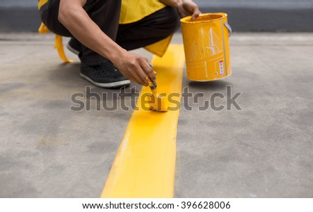 Man painting the yellow line on the concrete floor at car park - stock photo